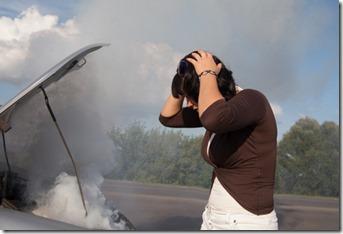 Woman looking at smoking car engine